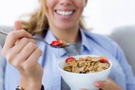 Bella giovane donna mangiare cereal...