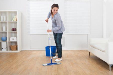 Donna pulizia pavimento in legno du...