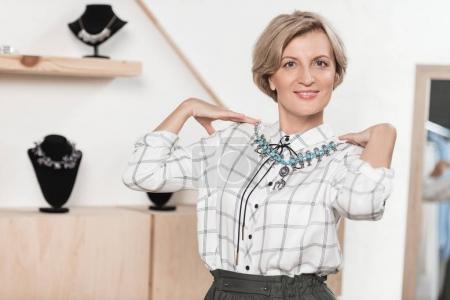 Donna che prova su collana in negoz...
