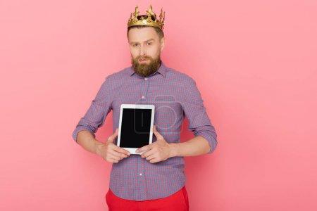 uomo con corona che tiene tablet di...