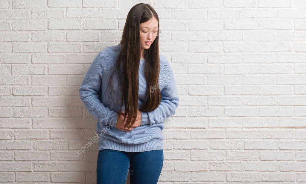 Ipastock donna giovane partner sopra il mattone bianco della parete con la mano sullo stomaco - La mano sullo specchio ...