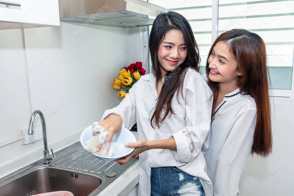 Ipastock due donne asiatiche lavare i piatti insieme in for Stili di cucina