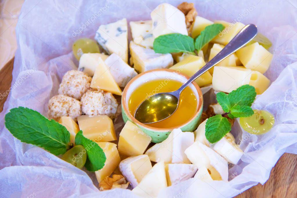 Ipastock piatto con diversi tipi di formaggio su carta bianca con miele decorato con foglie di - Diversi tipi di carta ...