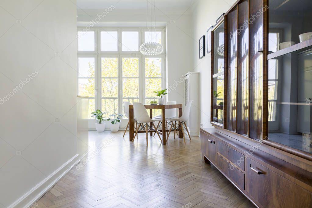 Ipastock - Mobile in legno all'interno della luminosa sala da pranzo con sedie bianche al tavolo ...
