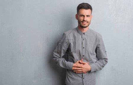Ipastock giovane uomo adulto in piedi sopra la parete grigio grunge con la mano sullo stomaco - La mano sullo specchio ...
