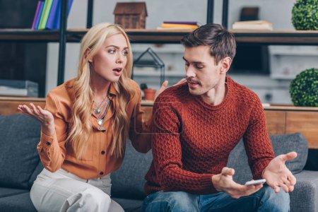Ipastock emotivo coppia arrabbiata che si siede sul divano e che litigano su smartphone - Coppia di amatori che scopano sul divano ...