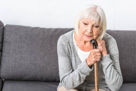 pensive donna anziana con canna di ...