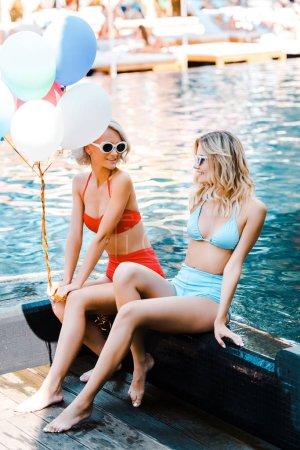 Ipastock donne attraenti in pin up costumi da bagno che tiene i palloni stando seduti a bordo - Donne che vanno in bagno a cagare ...