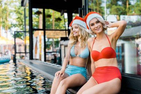 Ipastock belle ragazze in costumi da bagno e cappelli della santa che si siede a bordo piscina - Donne che vanno in bagno a cagare ...