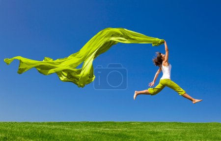 Woman jumping on a green meadow wit...